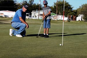 Jon Johnson Photo/Gila Valley Central: Teaching pro Ron Armbrust, left, shows his excitement for a good looking putt from student Manan Patel.