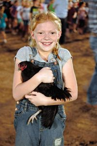 Jon Johnson Photo/Gila Valley Central: Kira Reed shows off the chicken she caught.