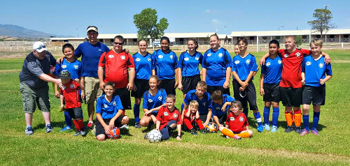 Contributed Photo: Courtesy of Hannah Keir/ The VIP team in their red uniforms pose for their first game alongside their co-players, the Blue Berries.