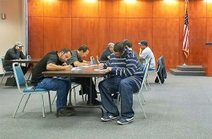 Photo By Kimberly Tremain: Applicants for construction jobs at the new Graham County Adult Detention Facility fill out paperwork during a hiring fair, Monday.