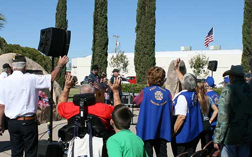 "Brooke Curley Photo/ Gila Valley Central: As Tribute sang, ""God Bless the USA"" the crowd stood up, holding hands and singing along."