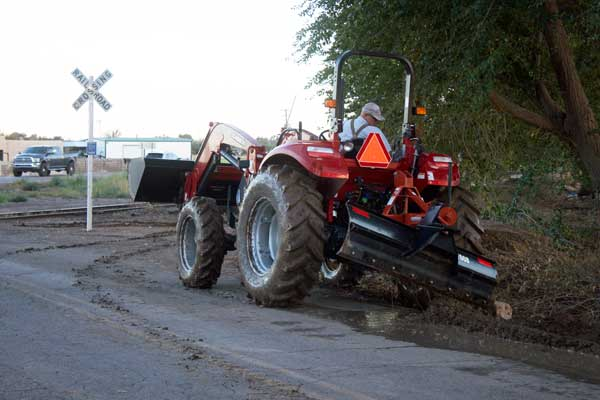 Jon Johnson Photo/Gila Valley Central: Bart Judd digs a trench with his tractor to alleviate his flooded corral.