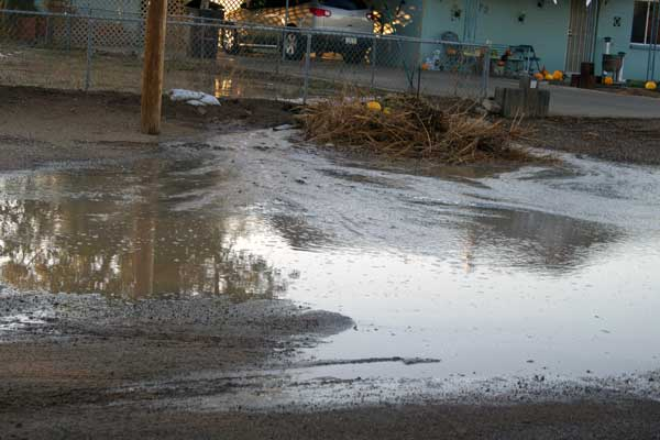 Jon Johnson Photo/Gila Valley Central: Water and debris pour out of a yard in Pima.