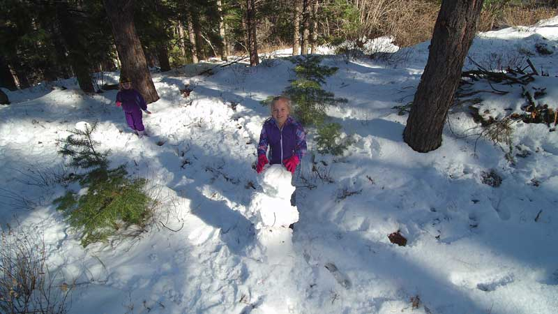 Jon Johnson Photo/Gila Valley Central: Ambrosia Johnson makes a snowman during an outing to Mount Graham on Dec. 26.