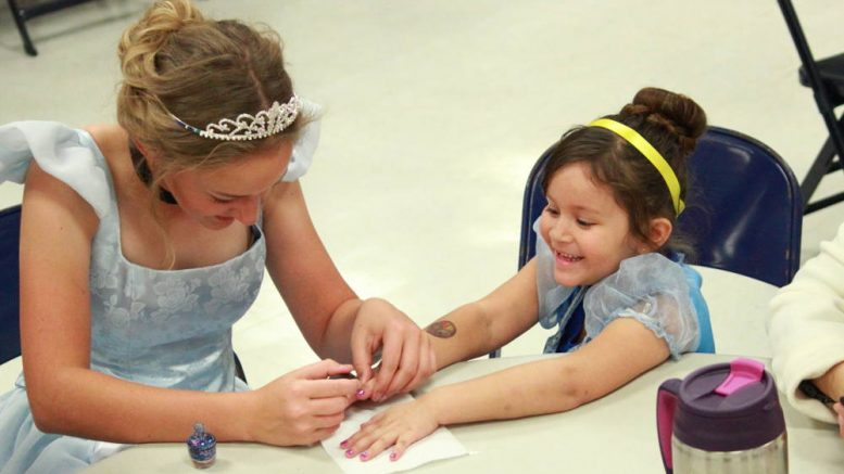 Eric Burk Photo/ Gila Valley Central: Cinderella paints Isabella Gonzales' fingernails purple at a Princess and Superhero Breakfast hosted by Safford High School's Taste of Sound Choir.