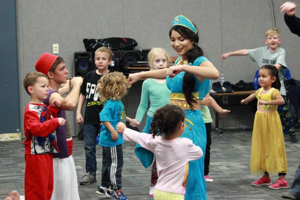 Eric Burk Photo/Gila Valley Central: Dressed as Jasmine, Taste of Sound Choir President Monica Larez leads children in a dance.