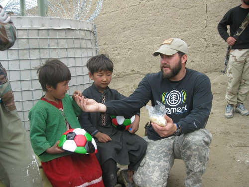 Contributed Photo/Courtesy Chris Taylor: Chris Taylor works with Afghan children during his service augmenting a Special Forces team.