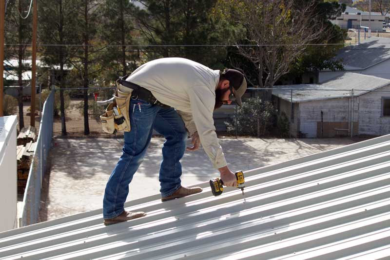 Jon Johnson Photo/Gila Valley Central: Safford Building And Maintenance  Department Employee Justin Hatch Zips Down The New Metal Roofing.