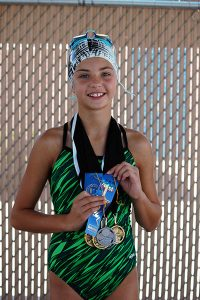 Jon Johnson Photo/Gila Valley Central: Thatcher's Avery Johnson shows off the assortment of medals and ribbons she acquired at the Gila Valley Summer League Finals.