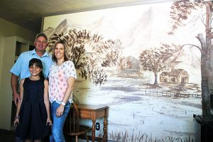 Jon Johnson Photo/Gila Valley Central: The Lazy Traveler owners and operators, from left, Jeff Taisto, Jaidyn Martinez and Frances Martinez stand in front of a mural of Mount Graham reportedly painted by a prison escapee while on the lam. The mural is in one of 14 rooms available for rent.