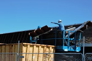 Jon Johnson Photo/Gila Valley Central: Workers move demolished material to a dumpster. The old Jerry Lewis Theater at the shopping center's southern end will be razed and paved.