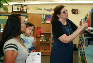 Photo: Brooke Curley/ Gila Valley Central.net: (From left to right) Preschool teacher Dorinda Mendez gets some information regarding a book from Safford Library Director, Leanne McElroy.