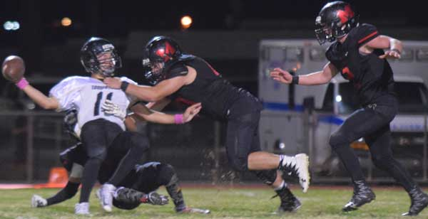 Photo By Raymundo Frasquillo: Gavin Chavez, on the ground, and Frankie Gonzalez (20) bring down Tombstone quarterback David Montoya (11) during a 2-point conversion attempt with 1:36 left in regulation and the score tied, 20-20.