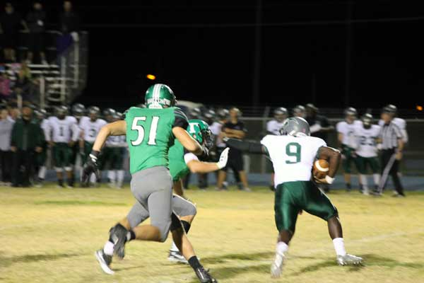 L. Scott Bennett Photo: Phoenix Christian's Tylin Rodgers attempts to stiff arm the Thatcher defender. The Eagles' defense stifled the Cougars all night.
