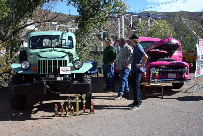 Photo By Walter Mares: Buzz Pilgrim, rear center, Jess Stillman and another man reflect on their entries at the second annual Clifton Festival of Lights Car Show held at the Post 28 American Legion in Clifton on Dec. 3. Stillman's entry is the light green 1966 Power Wagon. Pilgim's is the pink 1951 Ford pickup truck, which he had painted pink to raise awareness for breast cancer. Pilgrim is a cancer survivor. He also has relatives who died of the disease. Trophies in front of the vehicles were won at various car shows, including a major show in Silver City, N.M. The Clifton festival is in its 20th year.
