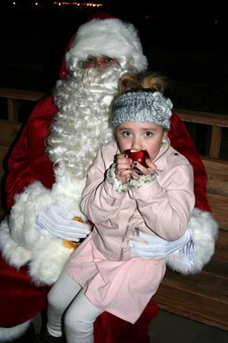 Photo By Walter Mares: This little girl is not distracted from her apple as she meet Santa Claus on Christmas Eve at Al Fernandez Park in Clifton. Clifton fireman were able to attract Santa Claus to Clifton to meet and greet many younger children. Fireman Hector Morales played a big part in bringing the jolly old man to Clifton.