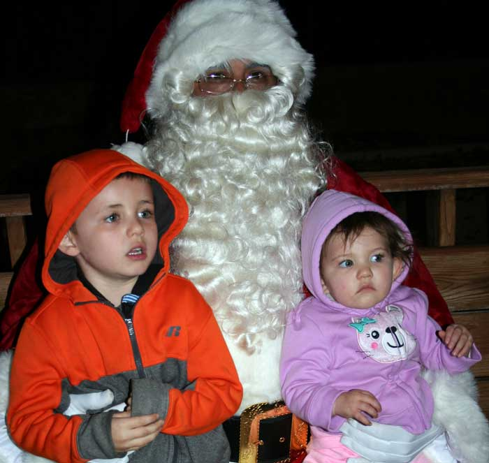 Photo By Walter Mares: This boy and girl are held by Santa Claus after they told him their Christmas wishes. The Clifton Fire Department brought Santa to Clifton to provide a special treat to the many children who visited with him.He held court in the gazebo at Al Fernandez Park in Clifton.
