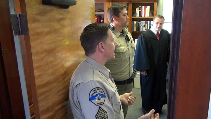 Jon Johnson Photo/Gila Valley Central: From left, GCSO Sgt. Jacob Carpenter and deputy Aaron Smith instruct Judge Michael D. Peterson on how to react to a threat.