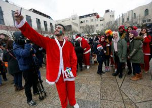 A Palestinian takes a picture with man dressed as Santa Claus at Manger Square, outside the Church of the Nativity, built atop the site where Christians believe Jesus Christ was born, on Christmas Eve, in the West Bank City of Bethlehem, Saturday, Dec. 24, 2016. (AP Photo/Majdi Mohammed)