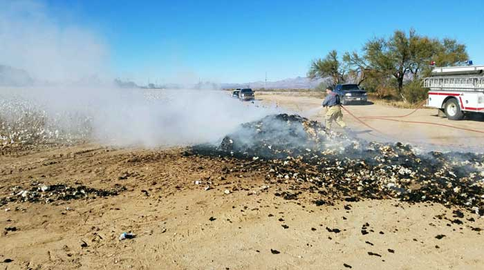 Contributed Photo/Courtesy Adam Hoopes: A Pima firefighter wets down a dumped load of cotton that was on fire.