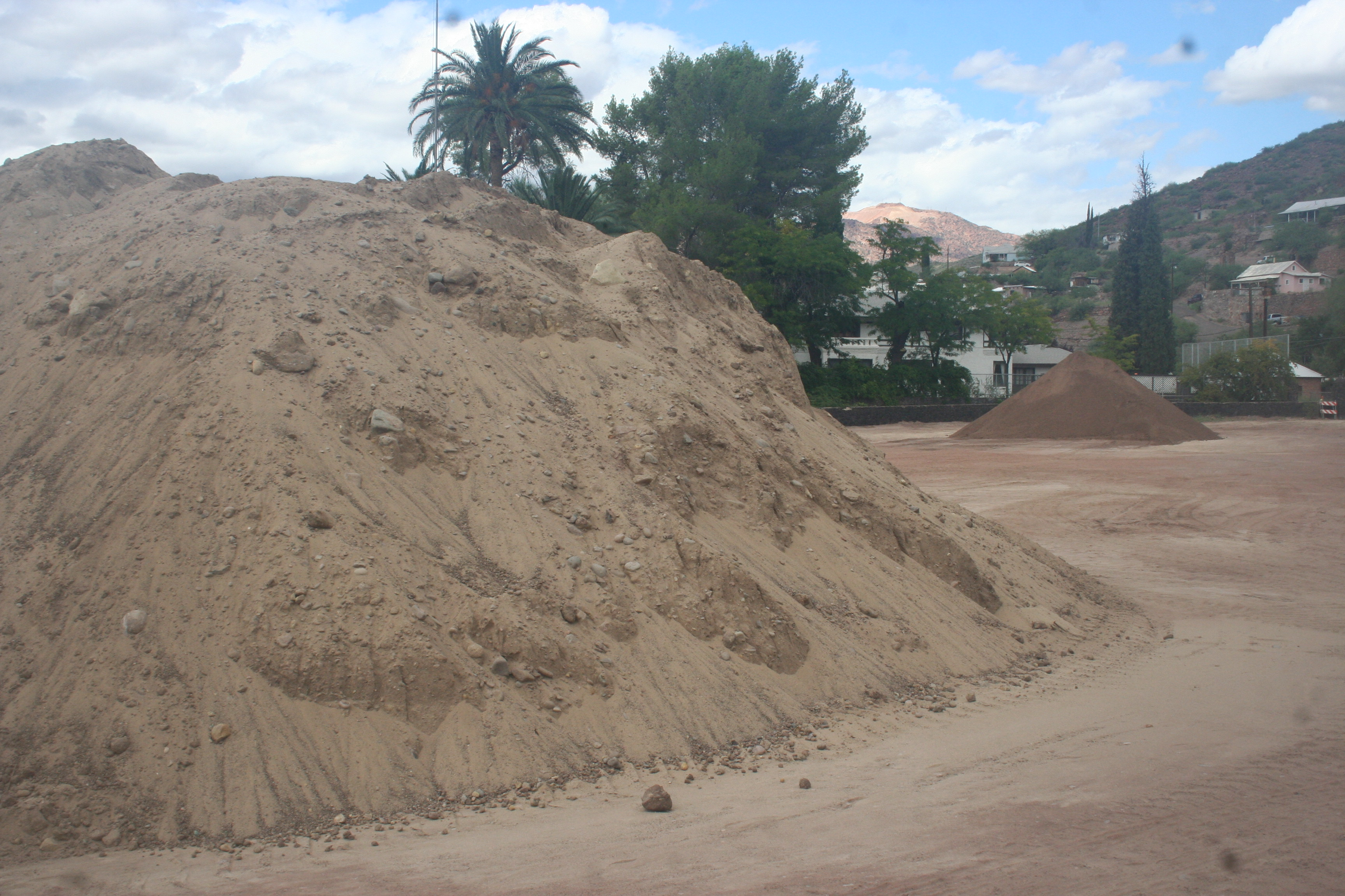 Photo By Walter Mares: Large piles of dirt are stashed in an open area next to the Freeport-McMoran, Inc. guesthouse while FMI installs a 25,000-gallon water recycling tank from which water will be used to irrigate Clifton's first-ever soccer field.  Water that drains from the adjacent splash pad will drain into the tank.