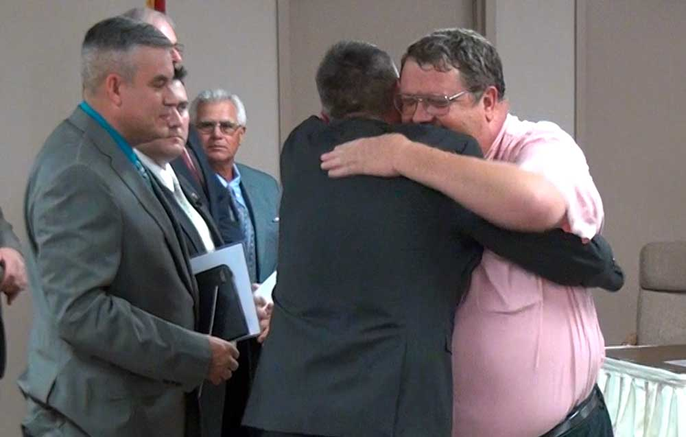 Jon Johnson Photo/Gila Valley Central: New Safford Mayor Jason Kouts, left, gives a hug to outgoing Safford Mayor Chris Gibbs.