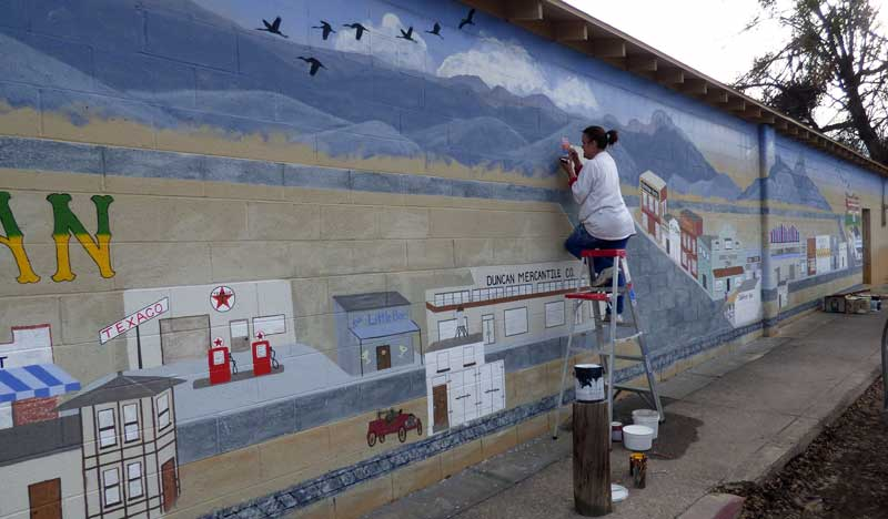 Photo By Dexter K. Oliver: Janine Eddy's latest mural shows the railroad track that led to Duncan's initial construction, main streets, schools and other buildings of the 1950s and their businesses.